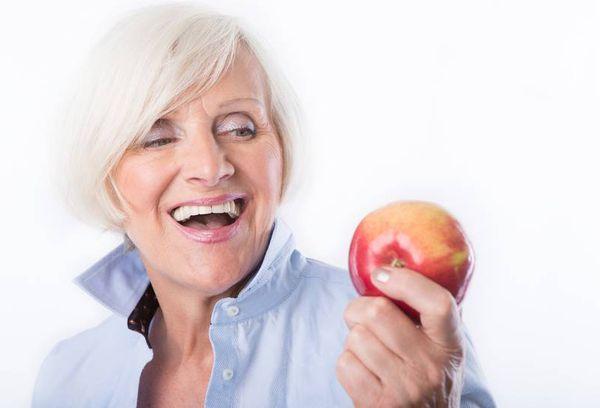 Пожилая женщина с яблоком