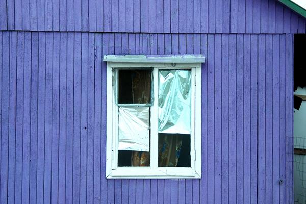 Старое окно с фольгой на стеклах